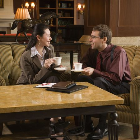 Caucasian mid adult businessman and woman drinking coffee and conversing. photo