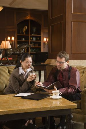 Caucasian mid adult businessman and woman drinking coffee and looking at  portfolio. Stock Photo - 2176131