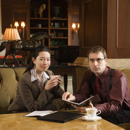 Caucasian mid adult businessman and woman drinking coffee and looking at viewer. Stock Photo - 2176079