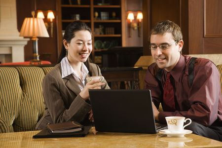 Caucasian mid adult businessman and woman drinking coffee and looking at laptop computer. photo