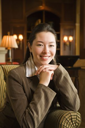 Taiwanese mid adult businesswoman smiling at viewer with chin resting on hands. Stock Photo - 2175936