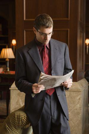 buisinessman: Caucasian mid adult buisinessman reading newspaper.
