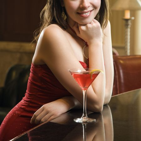 martinis: Taiwanese mid adult woman in red dress smiling and standing at bar with drink.