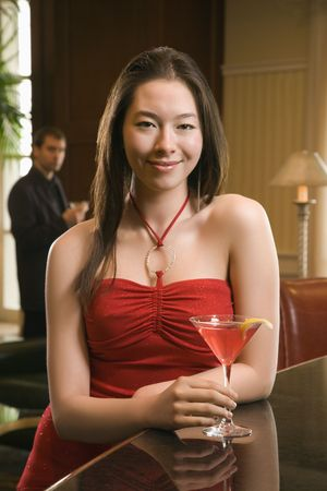 Taiwanese mid adult woman smiling and standing at bar with drink with businessman in background. Stock Photo - 2176102