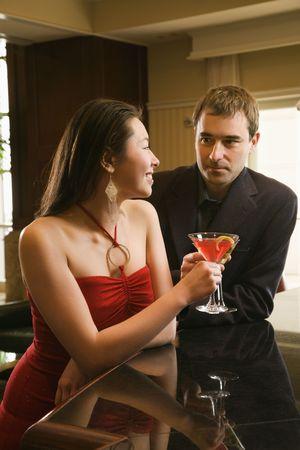 Taiwanese mid adult woman and Caucasian man at bar toasting martinis.