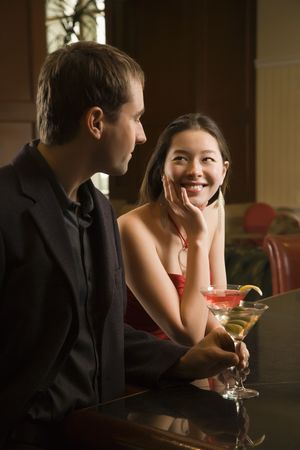 taiwanese: Taiwanese mid adult woman and Caucasian man standing at bar with drinks.