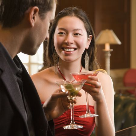adult dating: Taiwanese mid adult woman and Caucasian man toasting martinis. Stock Photo