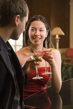 Taiwanese mid adult woman and Caucasian man toasting martinis. Stock Photo - 2204656