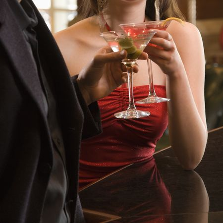Taiwanese mid adult woman and Caucasian man toasting martinis. Stock Photo