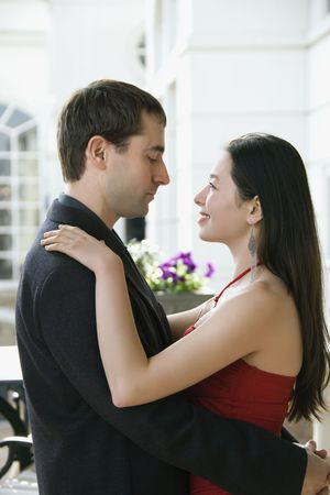 Taiwanese mid adult woman and Caucasian man embracing and gazing into each others eyes. Stock Photo - 2176217