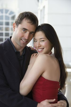 taiwanese: Taiwanese mid adult woman and Caucasian man outdoors embracing and smiling at viewer.