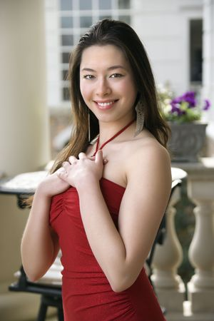Taiwanese mid adult woman in red dress standing outside smiling at viewer. Stock Photo - 2176194