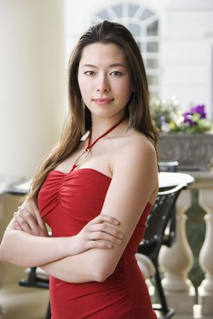 Taiwanese mid adult woman in red dress with arms crossed looking at viewer. Stock Photo - 2176169