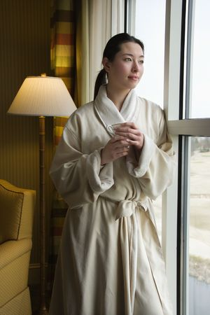 Taiwanese mid adult woman in bathrobe looking out window holding coffee cup. photo
