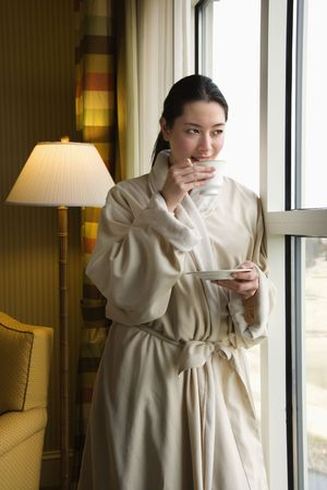 bathrobe: Taiwanese mid adult woman in bathrobe drinking coffee and looking out window.