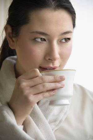 taiwanese: Taiwanese mid adult woman in bathrobe drinking coffee and looking to side.