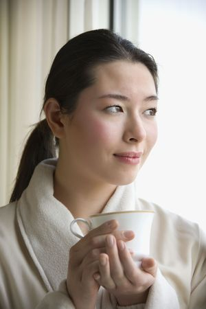 Taiwanese mid adult woman in bathrobe drinking coffee and looking out window. photo