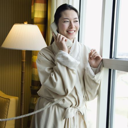 taiwanese: Taiwanese mid adult woman in bathrobe talking on phone and looking out window. Stock Photo