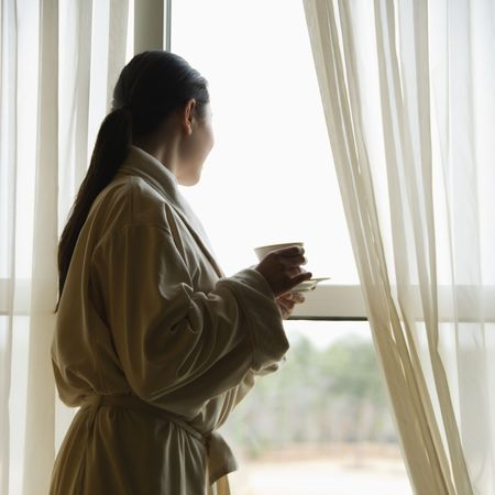 Taiwanese mid adult woman in bathrobe  looking out window. Stock Photo - 2176615