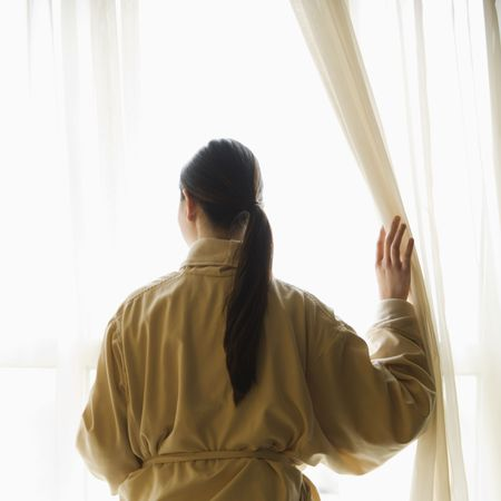 Taiwanese mid adult woman in bathrobe  looking out window. photo