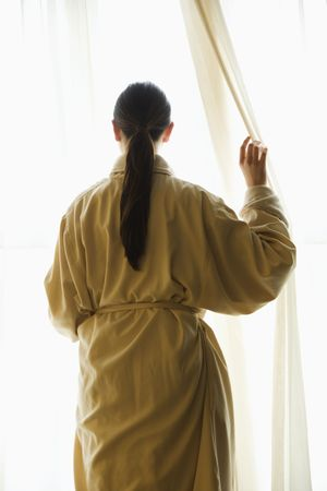 Taiwanese mid adult woman in bathrobe  looking out window. Stock Photo - 2176670