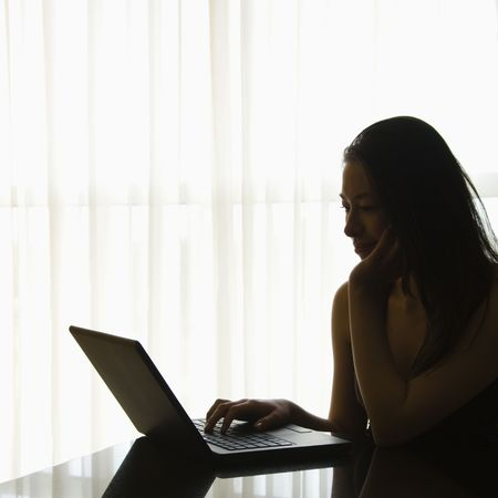 taiwanese: Silhouette of Taiwanese mid adult woman on laptop.