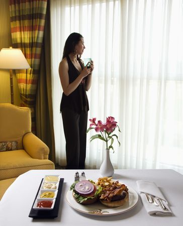 room service: Room service cheeseburger meal with flowers and Taiwanese mid adult woman in background.