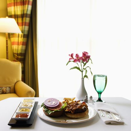 room service: Room service cheeseburger meal with flowers and condiments. Stock Photo