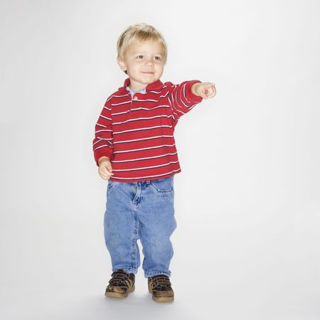 Studio portrait of Caucasian boy standing and pointing against white background. photo