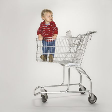 Studio portrait of Caucasian boy standing alone in empty shopping cart against white background.