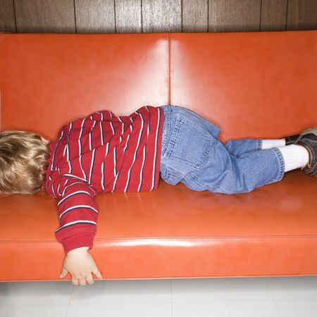 Caucasian boy sleeping on vinyl sofa.