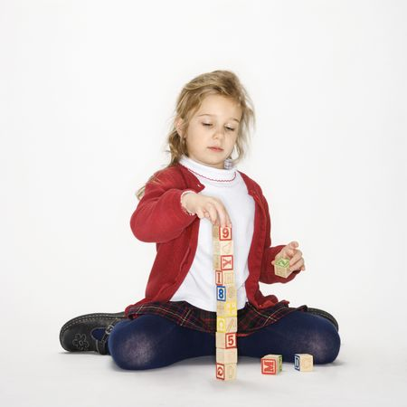 Studio portrait of Caucasian girl playing with toy blocks against white background. photo