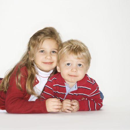 Studio portrait of Caucasian boy and girl against white background. photo