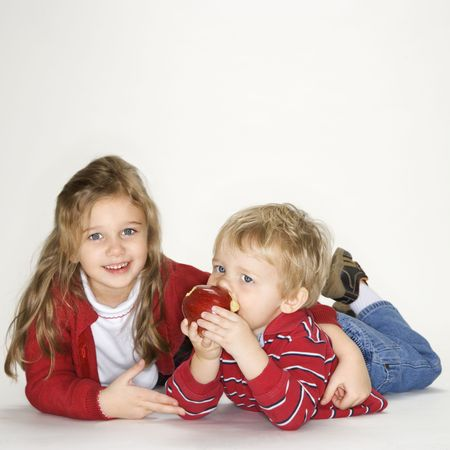 Studio portrait of Caucasian girl with arm around boy eating apple against white background. photo