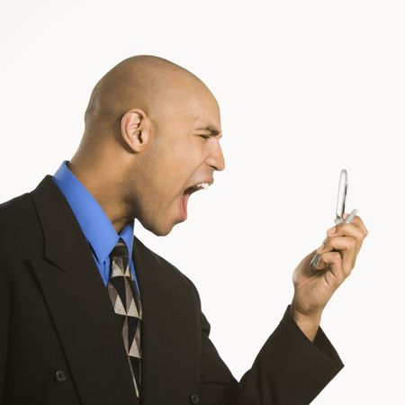 Head and shoulder portrait of African American man in suit yelling at cellphone. photo