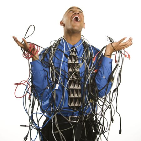 chaos: African American businessman wrapped in computer cables looking up with exasperation.