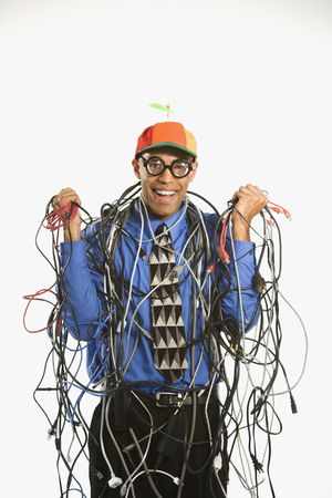 dork: African American businessman wrapped in computer cables wearing nerd hat and glasses.