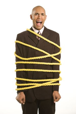 suppressed: African American businessman screaming wrapped in yellow rope. Stock Photo