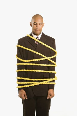 suppressed: African American businessman wrapped in yellow rope.