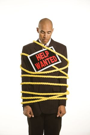 African American businessman wrapped in yellow rope wearing help wanted sign. photo