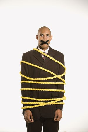 immovable: African American businessman wrapped in yellow rope with tape over  his mouth.