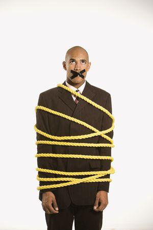 immobile: African American empresario envuelto en soga de color amarillo con cinta adhesiva sobre su boca.