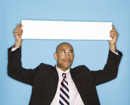 African American man holding blank sign against blue background. photo
