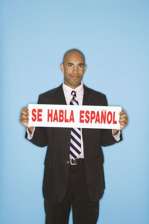 bilingual: African American man holding sign reading se against blue background.