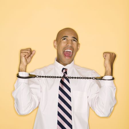 African American man wearing handcuffs and screaming. photo