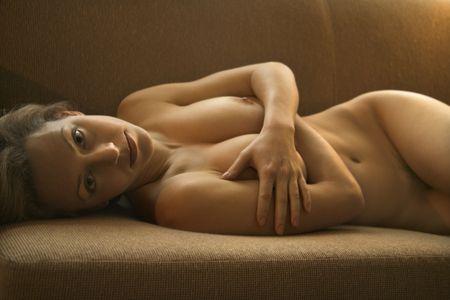half nude: Pretty Caucasian nude woman lying on back on sofa.