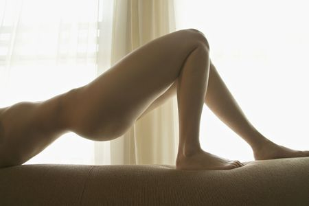 half nude: Caucasian nude woman arching in front of window. Stock Photo