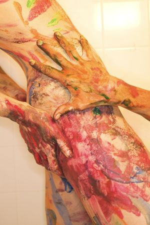 body paint: Young  female Caucasian adult painted with body paint and hand on her thigh.