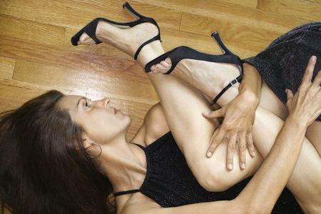 Caucasian mid adult woman lying on wood floor grasping legs of another woman. photo