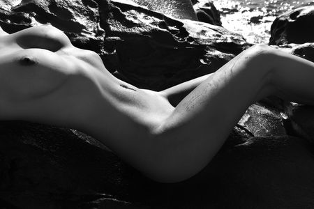 Close up of sexy Caucasian young adult woman sunbathing nude on rocks at Maui coast. Stock Photo